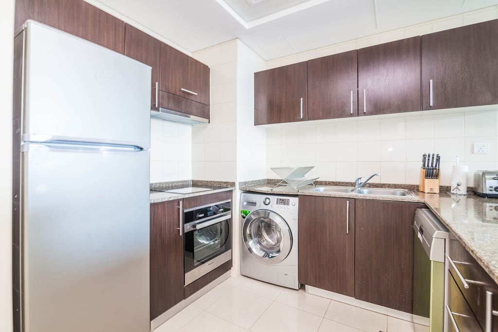 Fully-equipped kitchen with fridge freezer, cooker with halogen hob, microwave, dishwasher, coffee machine, and washing machine with tumble dryer.