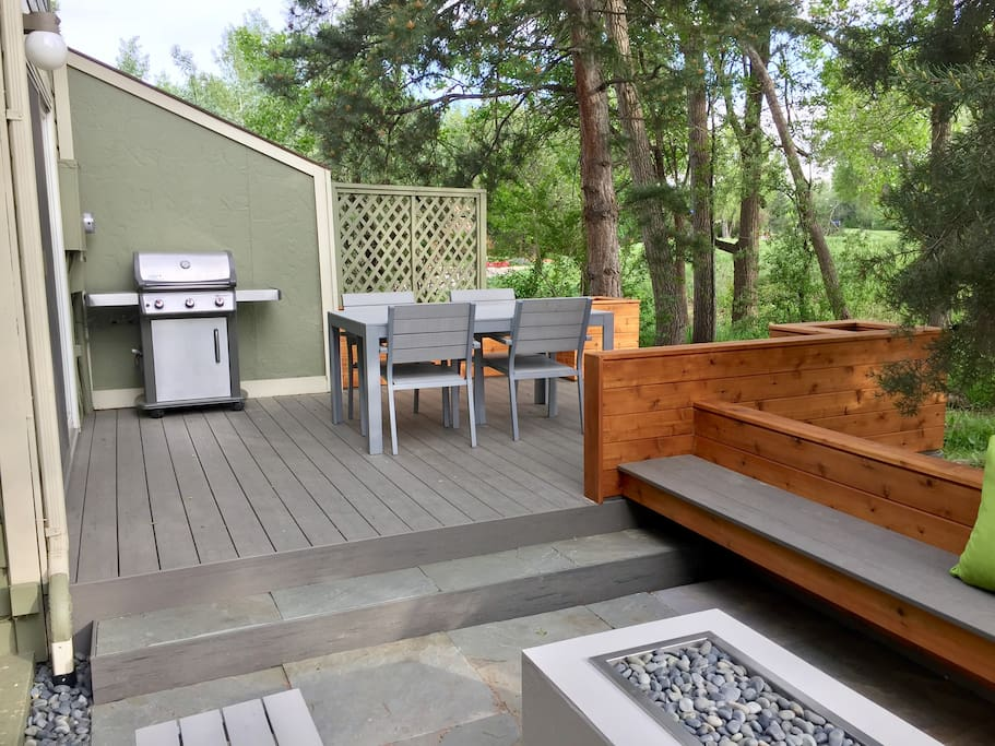 Brand new deck, outdoor dining table and gas grill in the backyard.