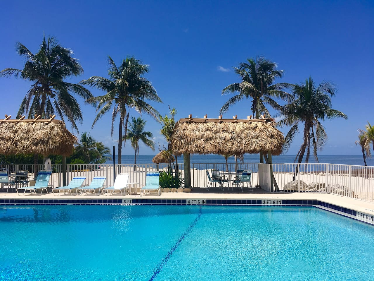 Oceanfront pool with tiki huts for shade