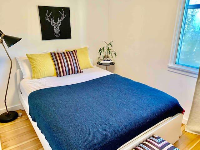 2nd bedroom with queen bed with window overlooking backyard