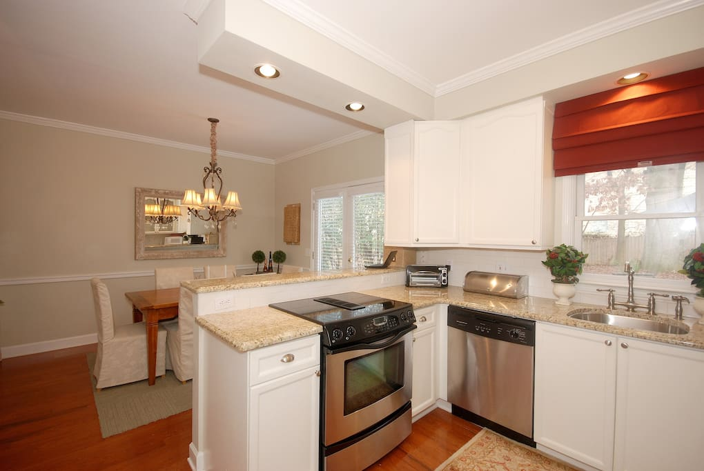 Kitchen with granite, stainless appliances, microwave and toaster oven.