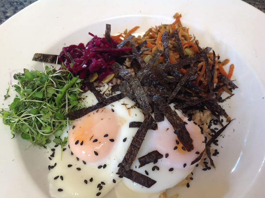Super food breakfast Black sesame brown basmatti rice, burdock and carrot saute, microgreens, poached eggs, homemade sauerkraut, nori, pumpkin seeds