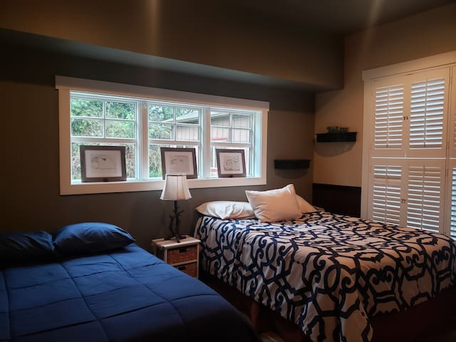 Large spacious bedroom with one Queen bed and one double. Both beds are Memory Foam mattress with down comforters in addition to decorative comforters. There is a TV with a built in DVD player