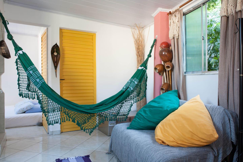 Quarto arejado com  e cama de casal e uma janela de frete  para um pomar de frutas tipicas do brasil.