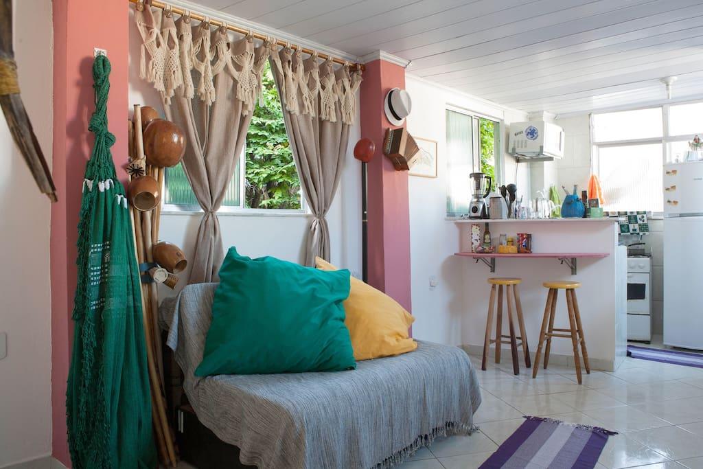 Sala e ao fundo cozinha com mesa para o café, Microondas, Fogão, Geladeira e maquina de lavar roupas.