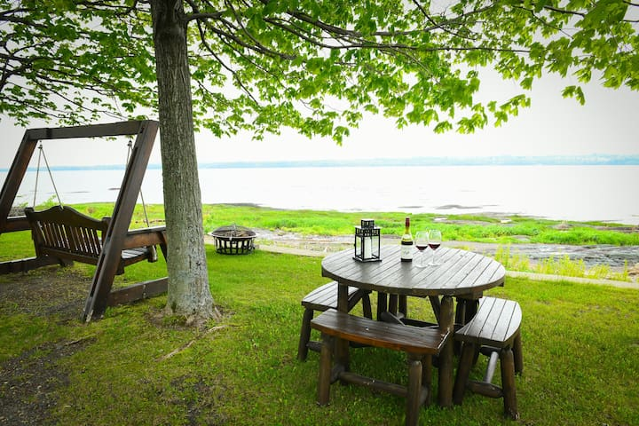 L'aménagement au bord du fleuve avec balancelle table et foyer rond. The riverside layout with table swing and round fireplace.