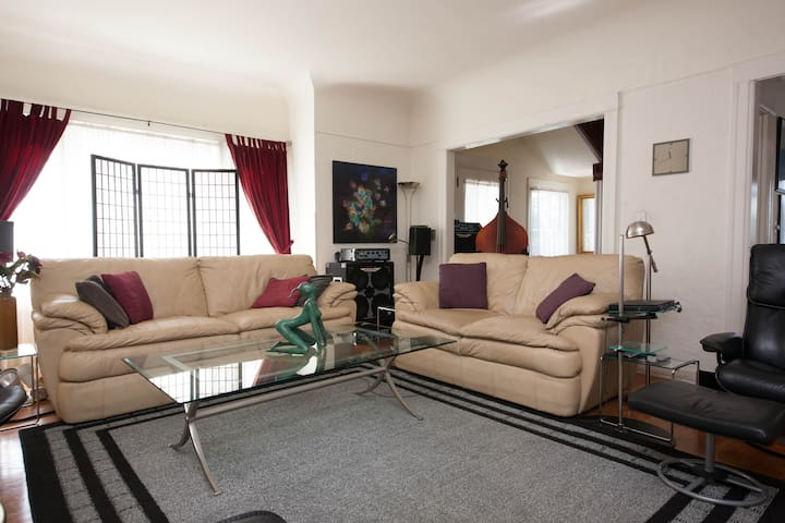 The living room is furnished in modern leather, glass and chrome
