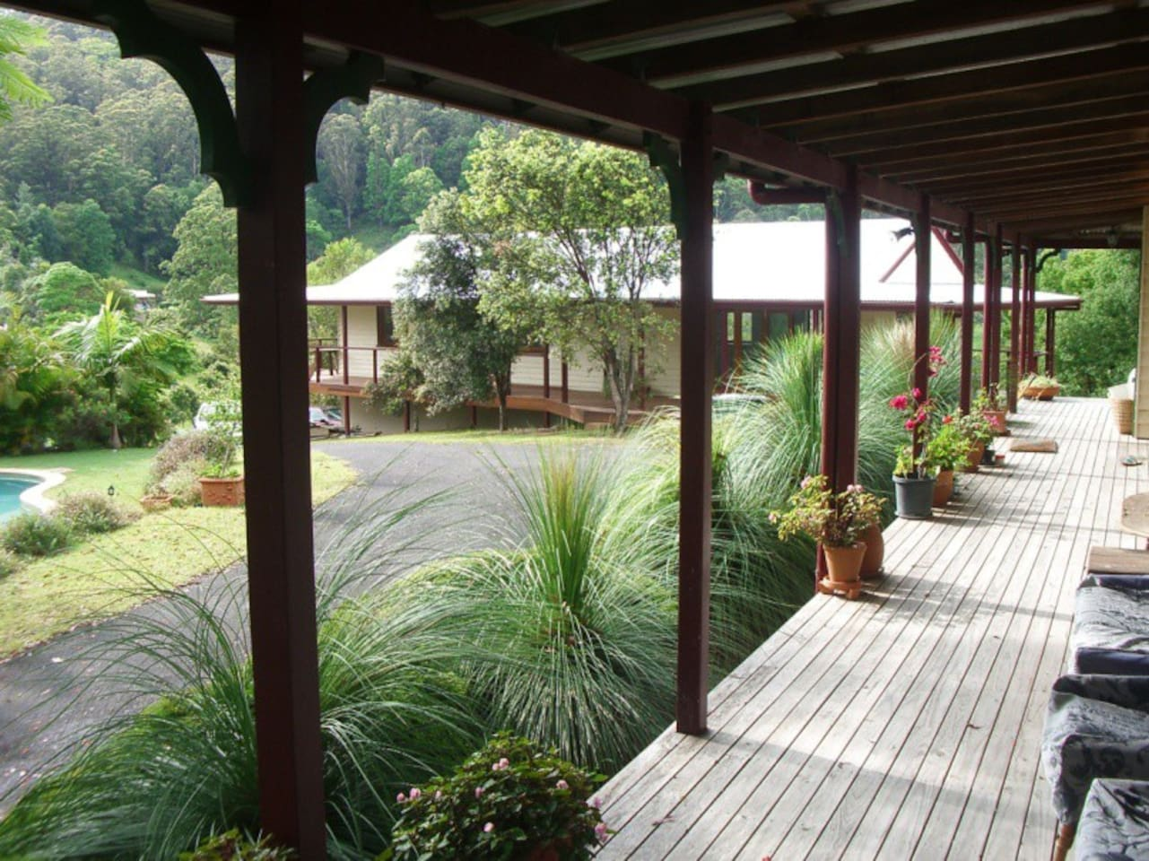 The two buildings on the property. Barracks is in the background. Verandah of main house in the foreground.