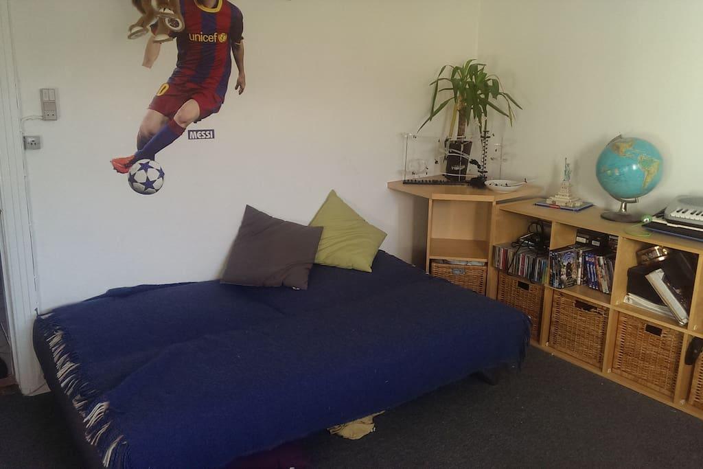 Ekstra stor værelse med sovesofa, tv og udsigt til have.