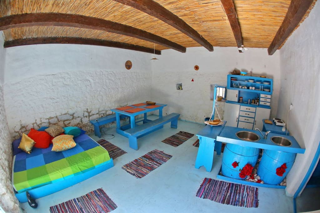 Summer kitchen with double sofa in the ground floor place for rest and chill. It has an exit at the outdoor court.