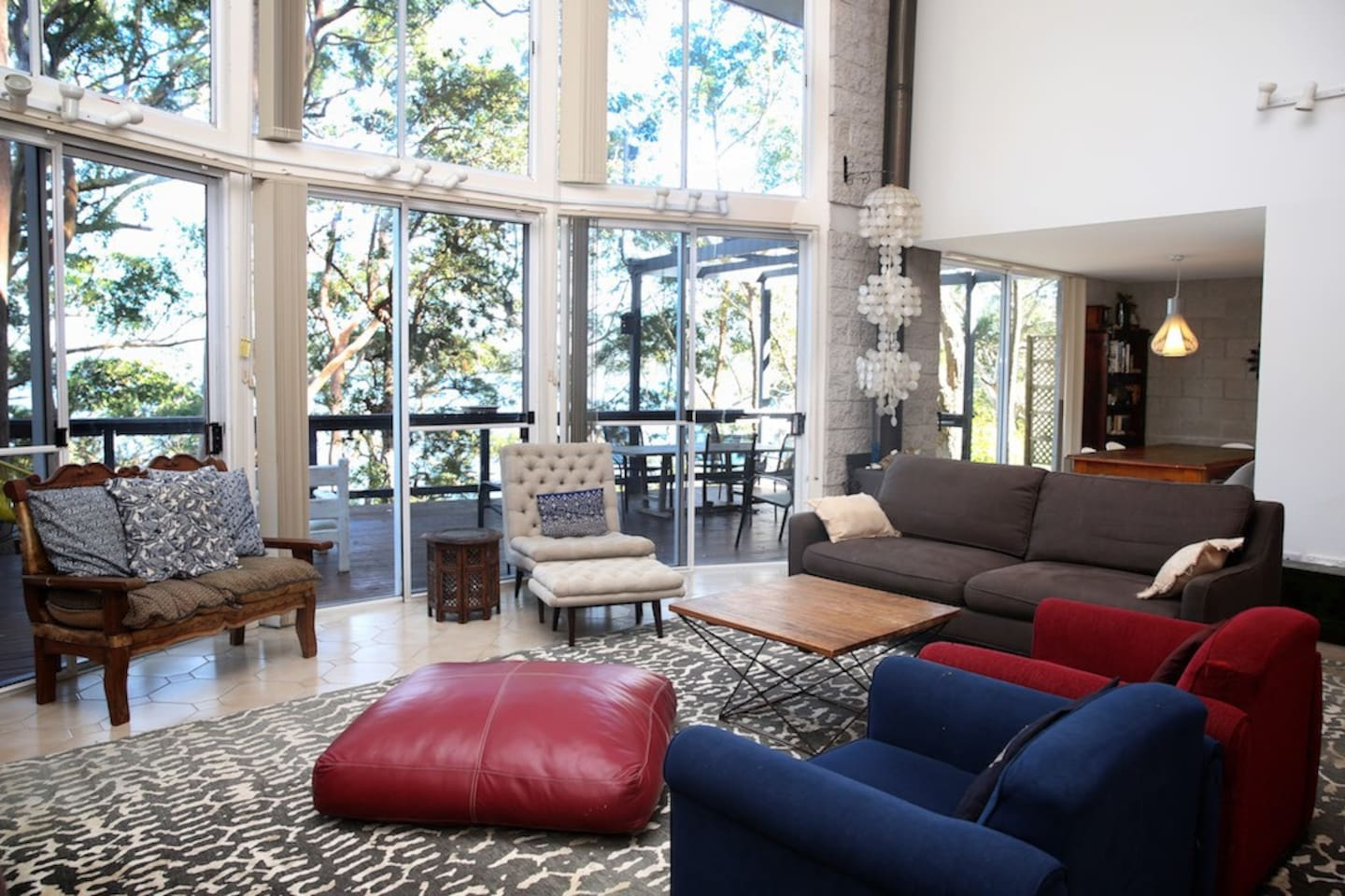 Large comfortable living area with double height windows overlooking the lake