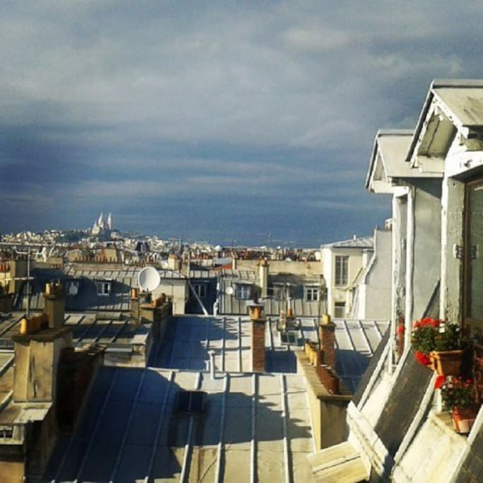 The view from the window on the roofs and Sacré Coeur - daytime