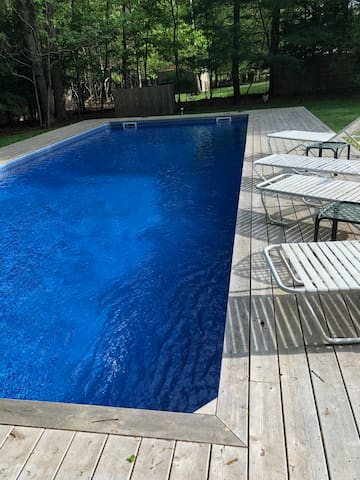 New sunny sparkling pool  with wrap around deck and lots of lounge chairs