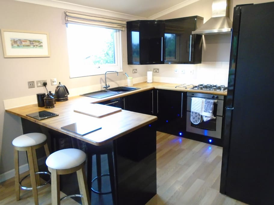 The contemporary kitchen has wooden worktops and is fully equipped.