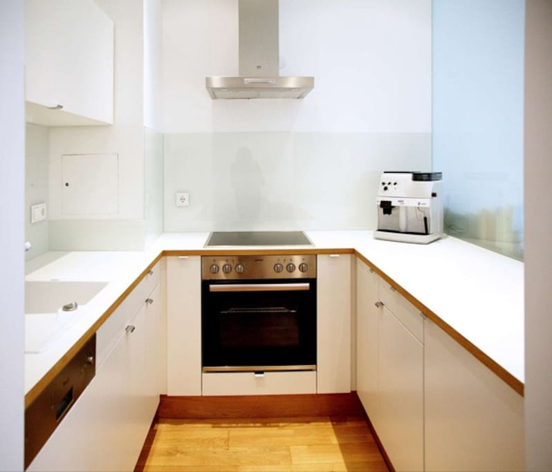 A fully equipped kitchen with dish washer, oven, cattle, espresso machine, fridge