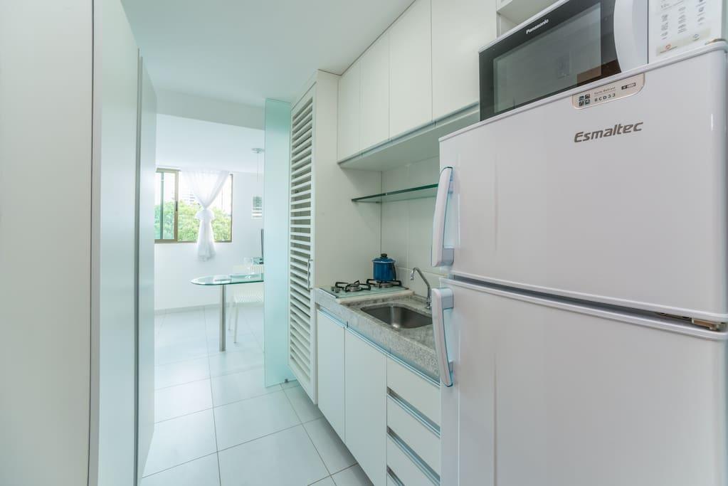 (Kitchen with fridge and microwaveCozinha com Geladeira; fogão 2 bocas, vários móveis.
