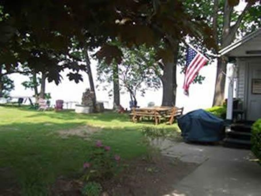 Large yard with chairs, grill, and 220 feet of lake front view