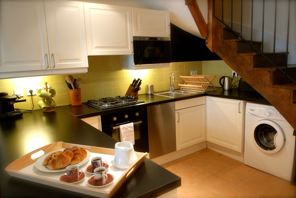 Fully-equipped, working kitchen with oven, microwave, coffee-maker fridge and washing machine.