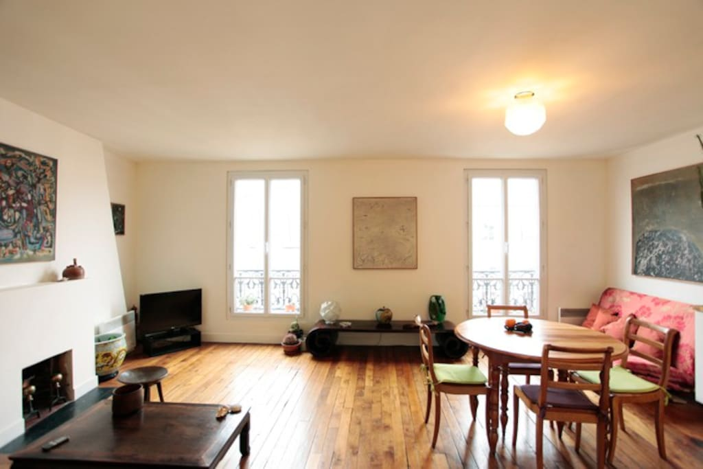 The entire apartment has a warm feeling with its wooden sculptures and other types of artwork.
