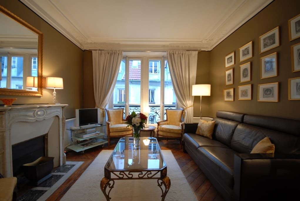The living room features an original marble fireplace and has a double window looking onto the quiet street below. There are three comfortable armchairs along with a leather sofa which converts to a full sized double bed with spring mattress which can sle