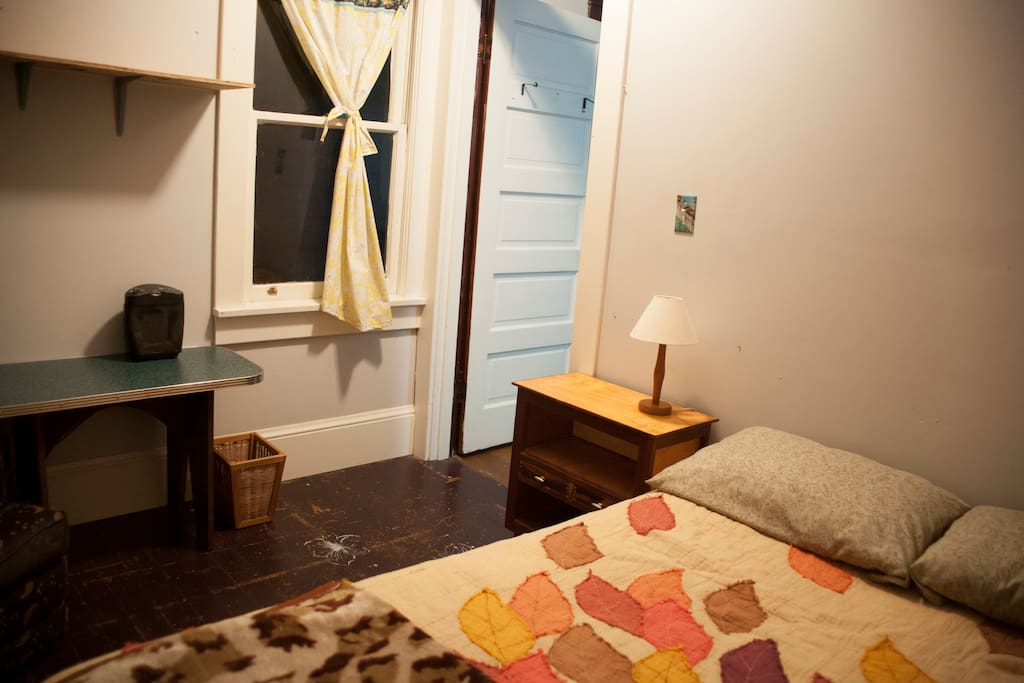 Full Bed and Side Table with drawers and shelves and small lamp.