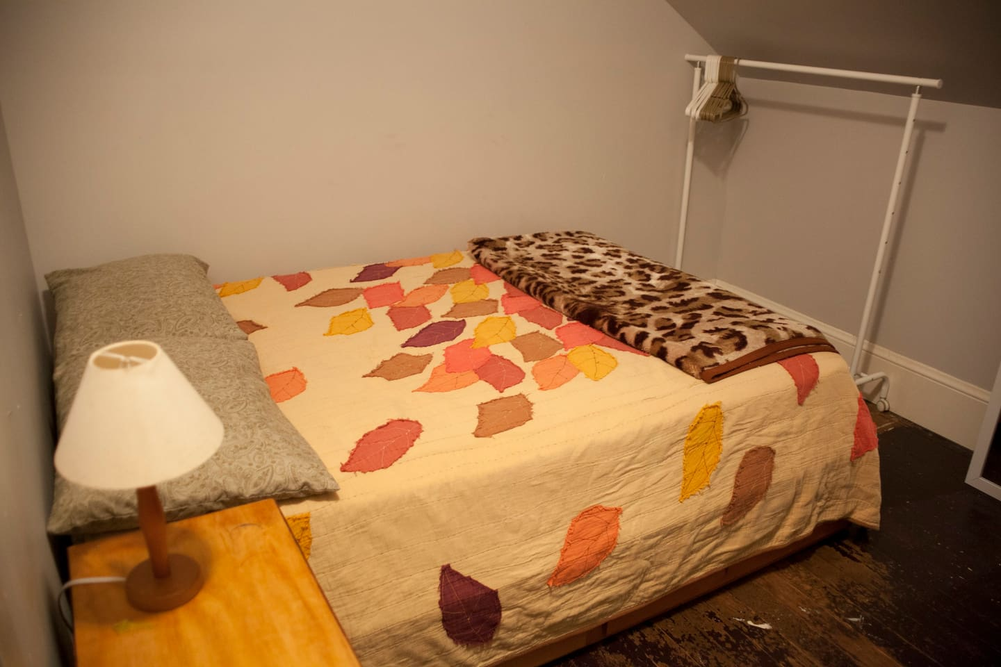 Full Bed, Side Table, and Clothing Rack with shelf space for suitcase and room for shoes.
