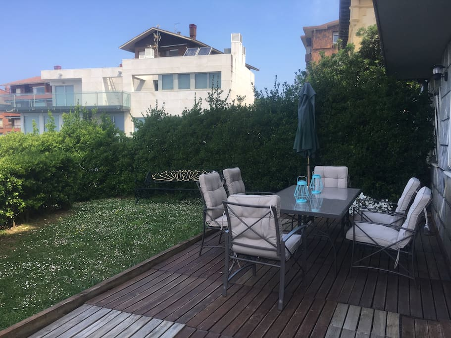 Jardín del apartamento con mesa de comedor , sombrilla y luz exterior.