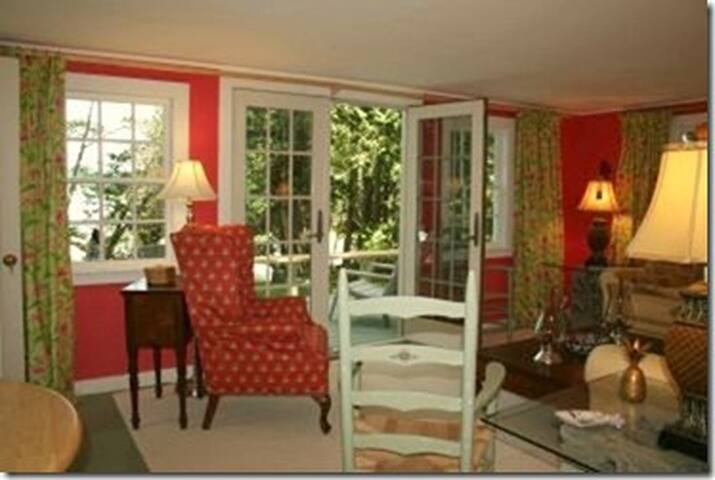French doors open to a deck with Adirondack chairs and a view of bay