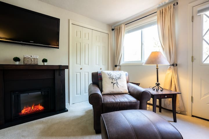 Master bedroom fireplace with cozy chair, balcony and comfortable large king bed