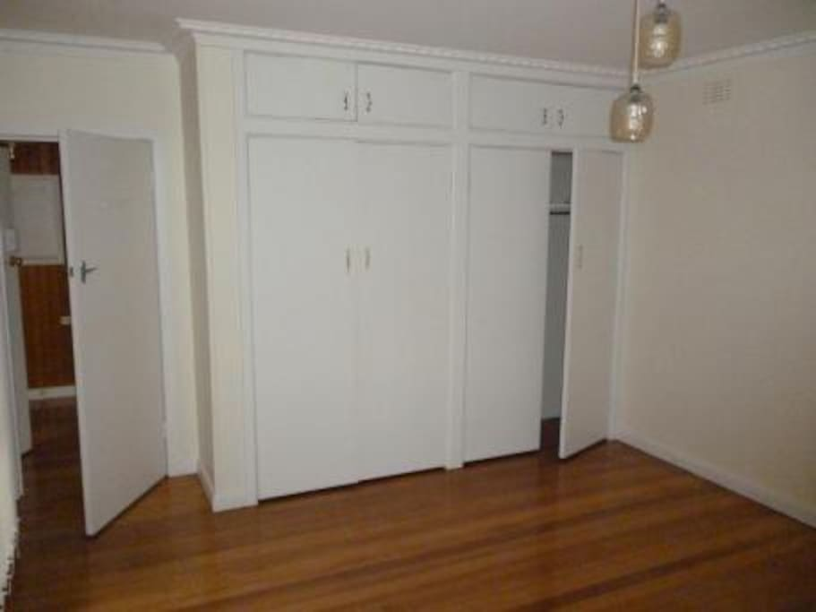 Spacious and bright master bedroom with plenty of storage space and polished boards