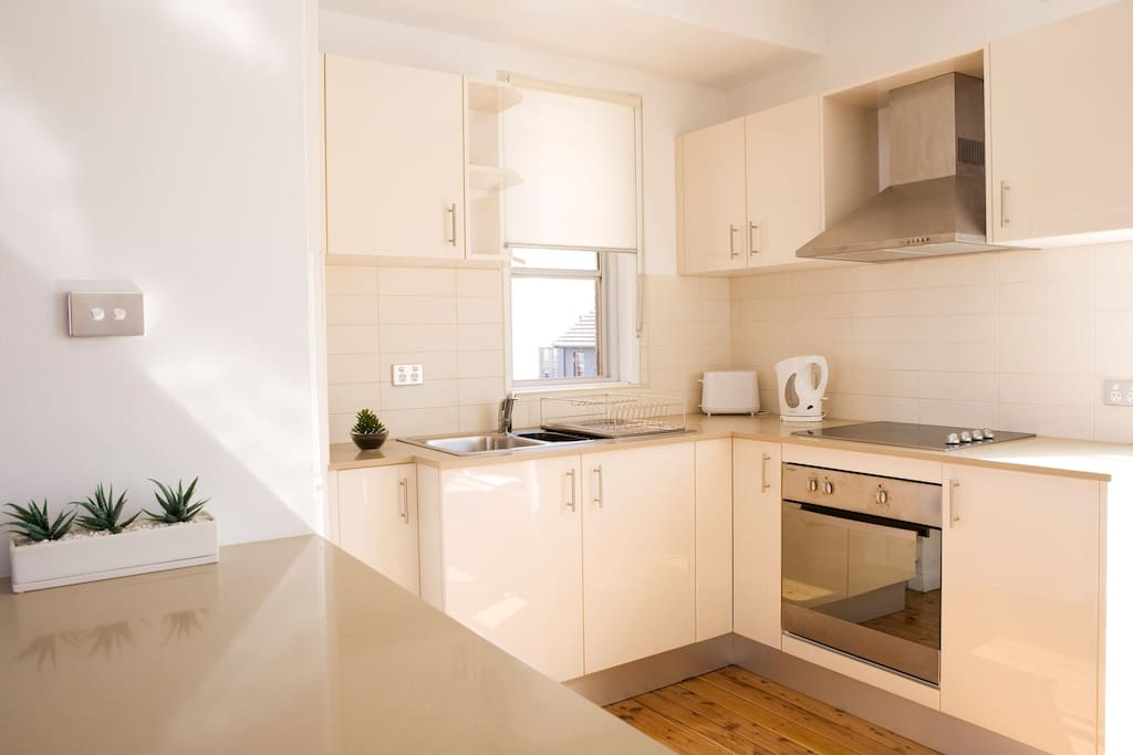 Kitchen with electric stoves, oven, microwave and fridge.