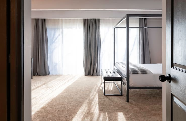 The master bedroom has a lot of natural light and a king size bed.