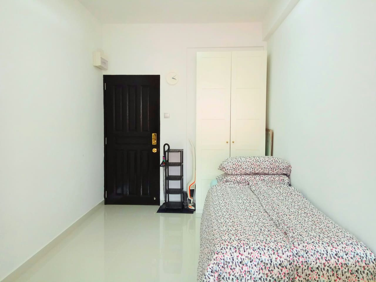 Clean, bright space with private entrance secured by digital lock, shoe rack and umbrella stand, wardrobe and bed.