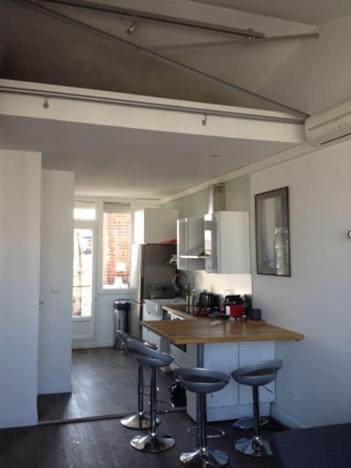 La cuisine/bar est tout équipée, la porte de la terrasse donne sur la cuisine