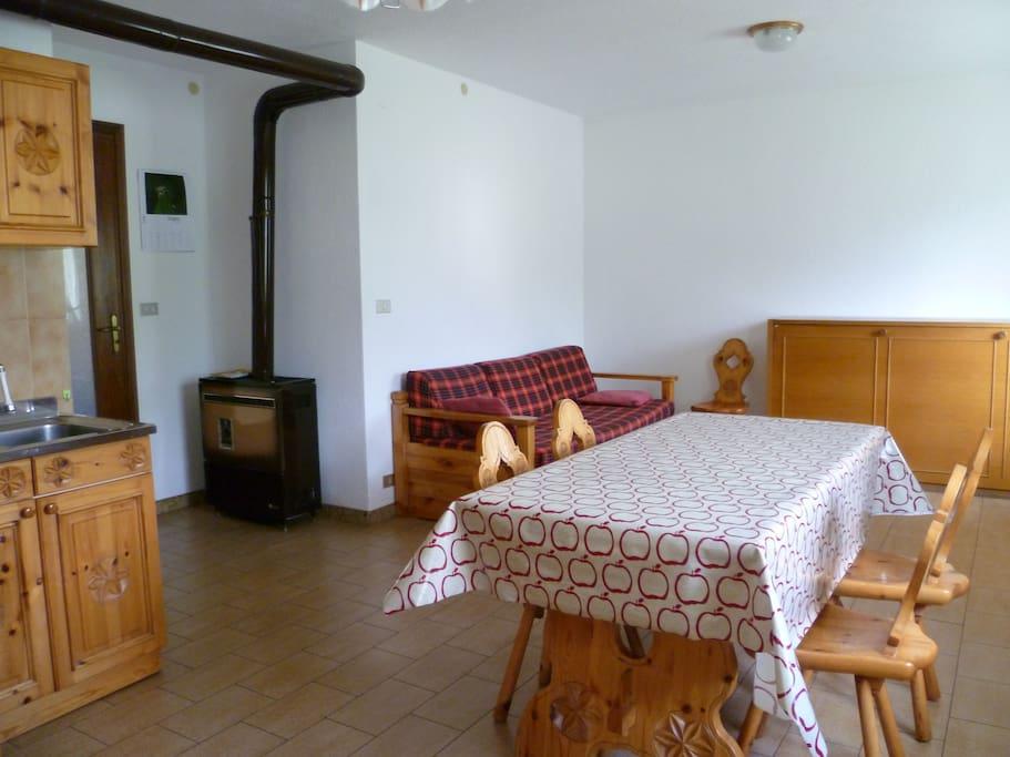 Ampio soggiorno con stufa a legna per l'inverno e  divano letto matrimoniale.