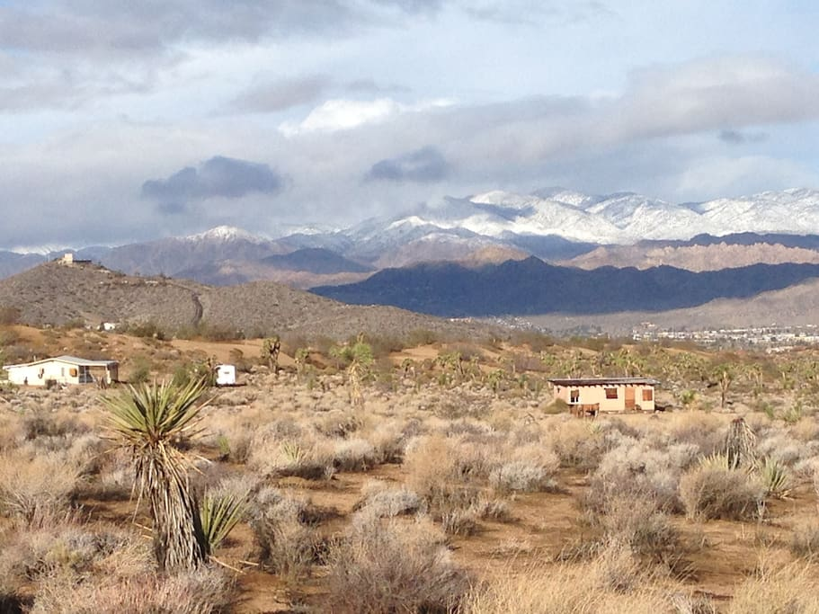 Desert Dharma Cabin at left, with snow capped mountains and Yucca Valley in valley below