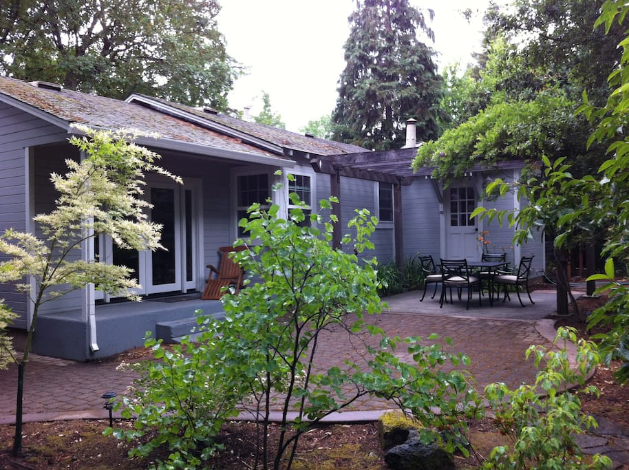 Large backyard patio with a gas grill, shady outdoor dining set and fully landscaped backyard with redwood trees.