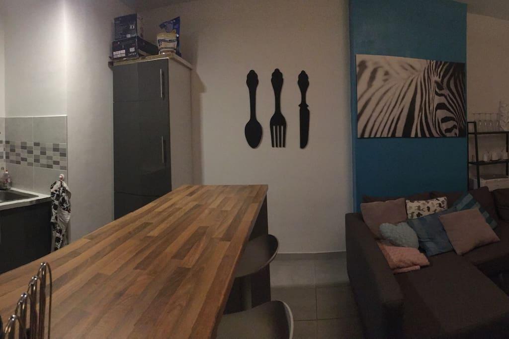 Bar/table à mangé équipé de 4 chaises hautes. Grand frigo et congélateur, four, et équipements de cuisines.