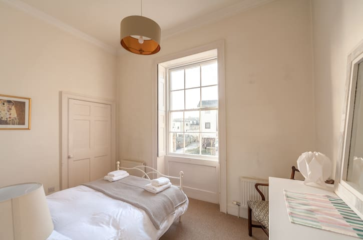 Large, light and quiet master bedroom with a double bed.