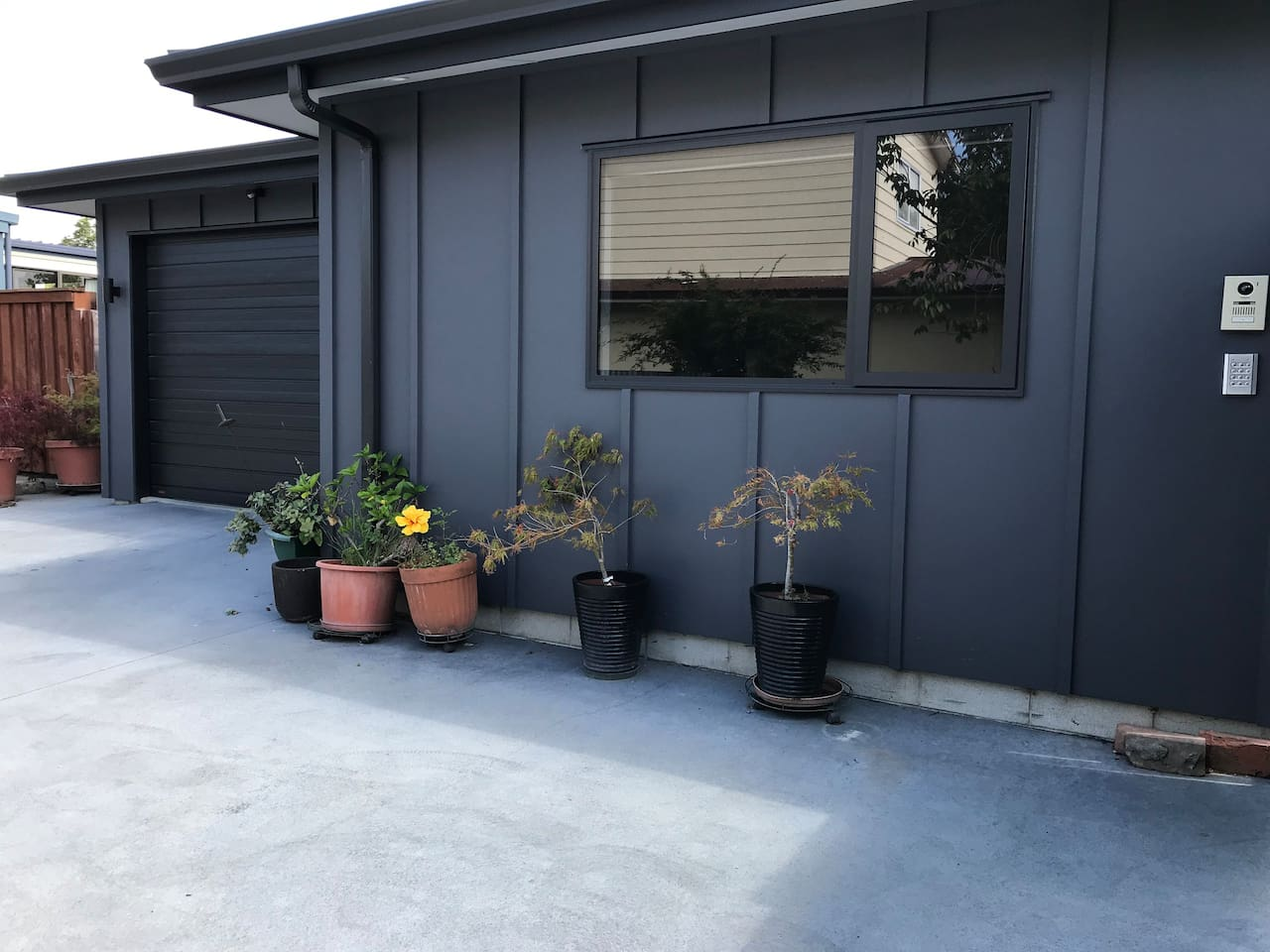 My home. Garage with access to the house an parking space for a second car under this window .Access keypad on the wall with bell