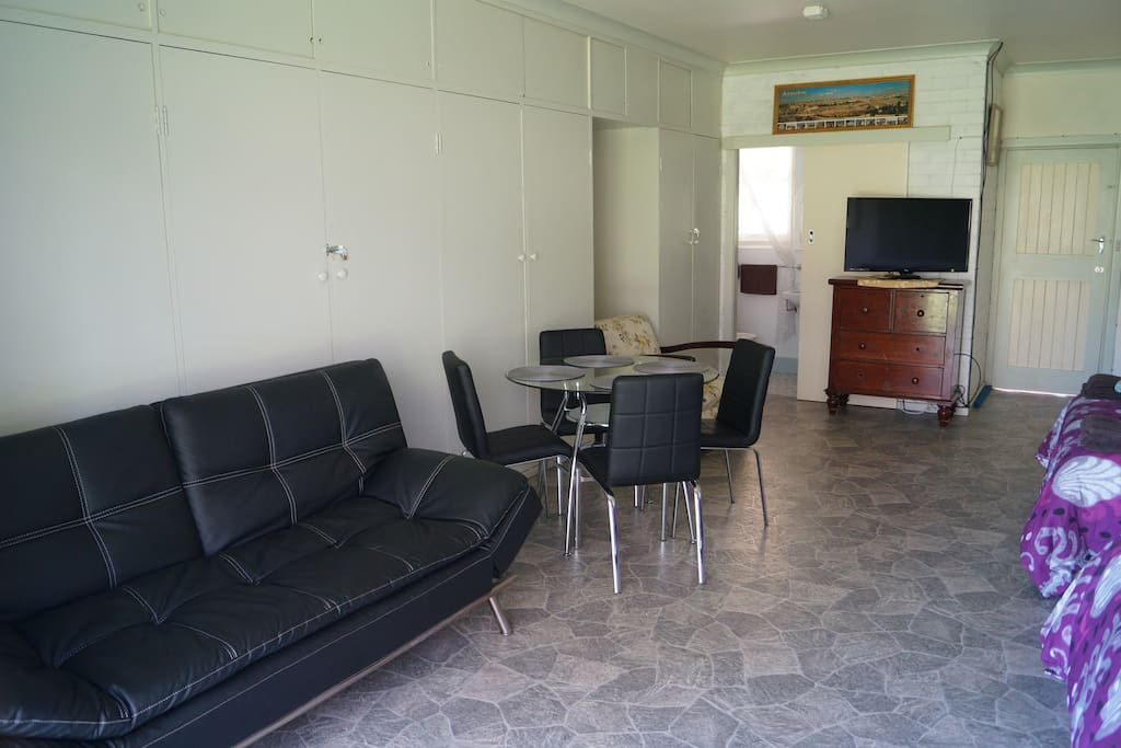 Looking into your room with sofabed/lounge and table with four chairs.
