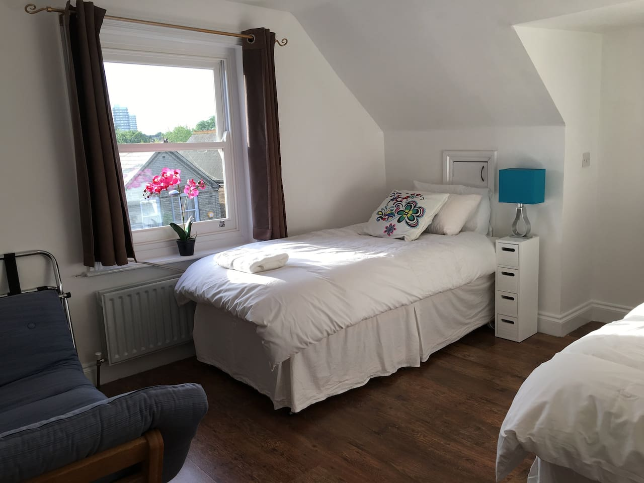 Bright and airy bedroom with 2 single beds and a sofa. The beds can be linked as a full king-size double at guest request