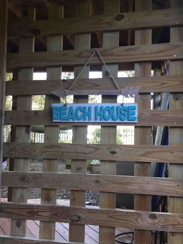 """The """"Beach House"""" sign guides you to the private entrance to our apartment, tucked away where you'll enjoy peace and quiet after a day on the beach or sightseeing."""