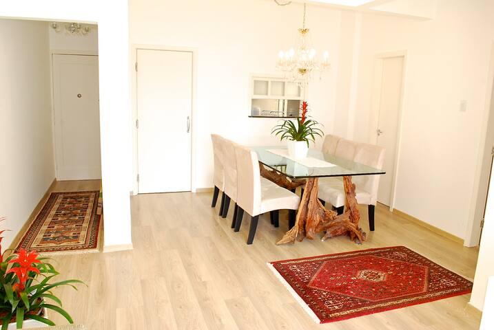 Sala de jantar com passa pratos p/ cozinha, belíssima mesa composta de  pés de madeira com forma de galho e tampo em vidro temperado.