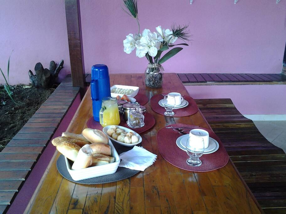 Café da manhã servido na área externa onde temos fogão à lenha e churrasqueira, mesa de jogos e jardim.