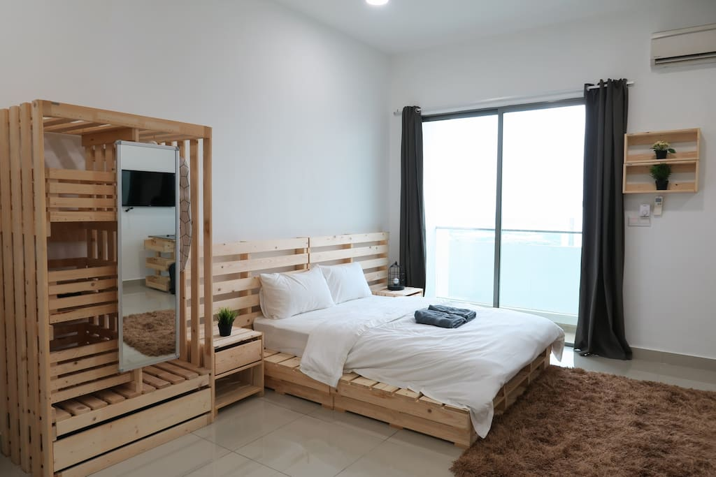 A spacious bedroom with 1 queen size bed and a wooden open wardrobe.