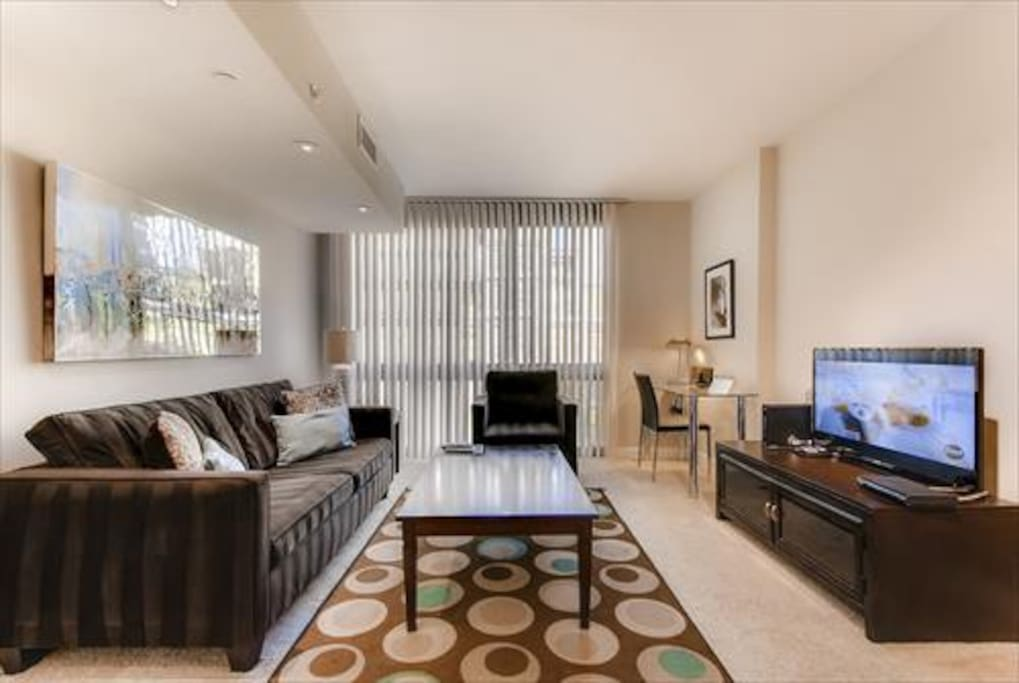 Spacious living room with seating area, entertainment center and dining area