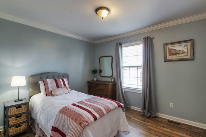 This room offers a twin bed with vintage tiger wood dresser and mirror along with a walk-in closet.