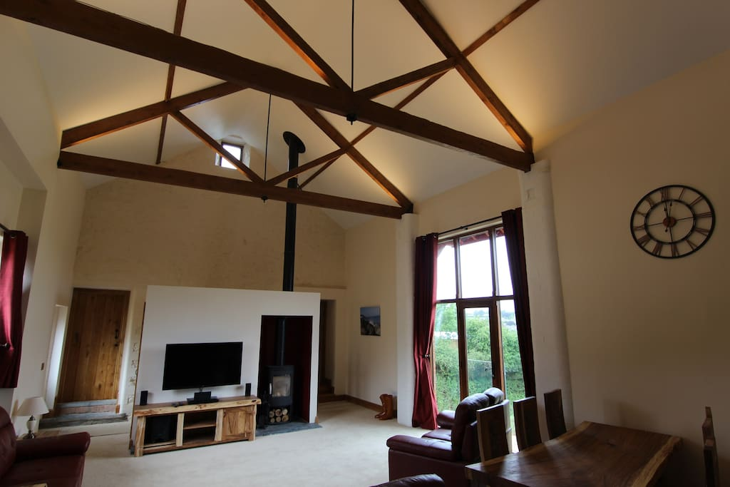 The lounge with vaulted ceiling, log burner and views across the village