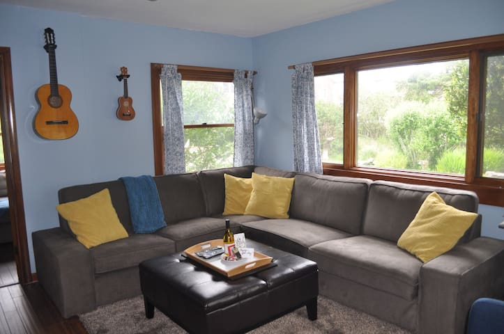 """Spacious open concept living room with giant sectional great for entertaining large groups or watching the 65"""" LED TV. New bamboo floors and carpets"""
